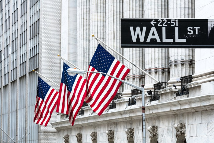 The exterior of an old building with three American flags and the Wall St. street sign in the foreground.