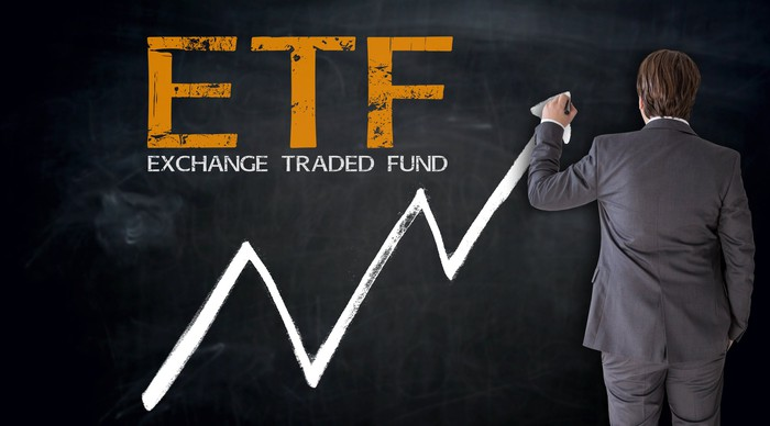 The letters ETF and Exchange Traded Fund on a blackboard, with a man in business suit drawing an arrow going up.