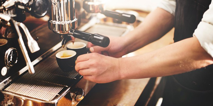 A barista in an apron using an espresso machine behind the counter