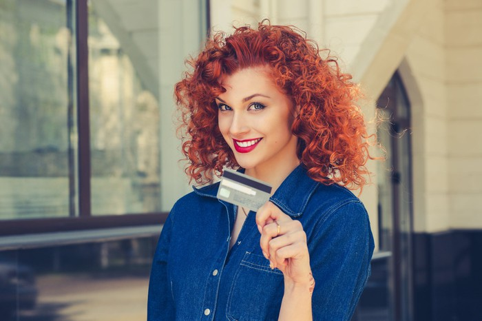 Smiling woman with red hair holding a credit card.