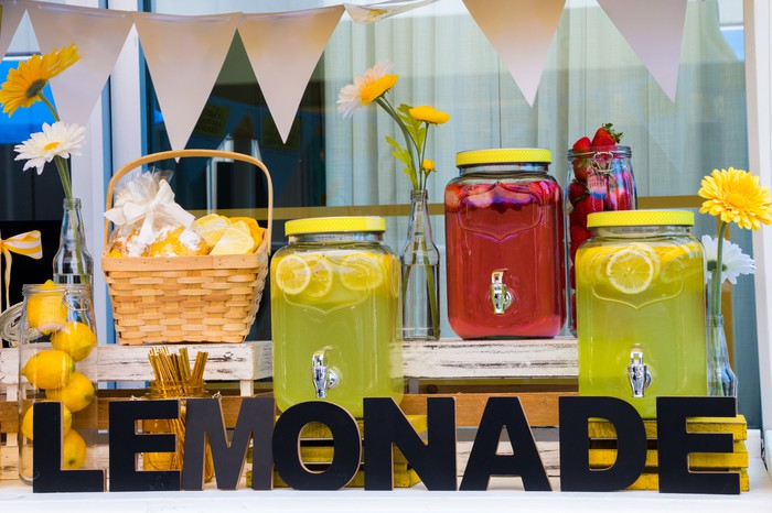 A lemonade stand with several serving jars of various lemonades.