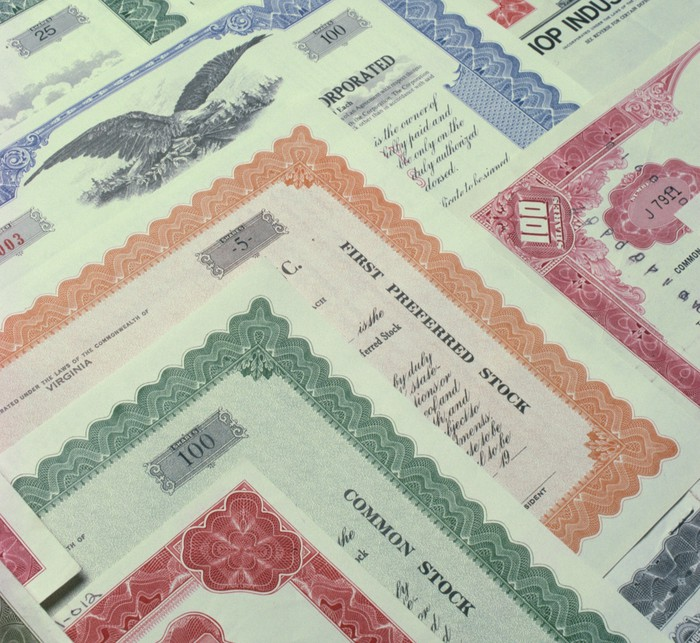 An assortment of colorful common and preferred stock certificates.