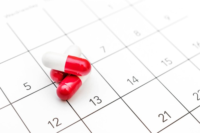 Red and while pills on top of a calendar