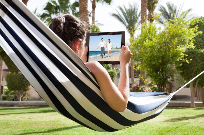 Woman watching a video on a tablet while in a hammock outside