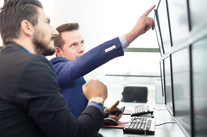 Man in a suit pointing up at one of multiple monitors while another man listens to him and looks at the same monitor.