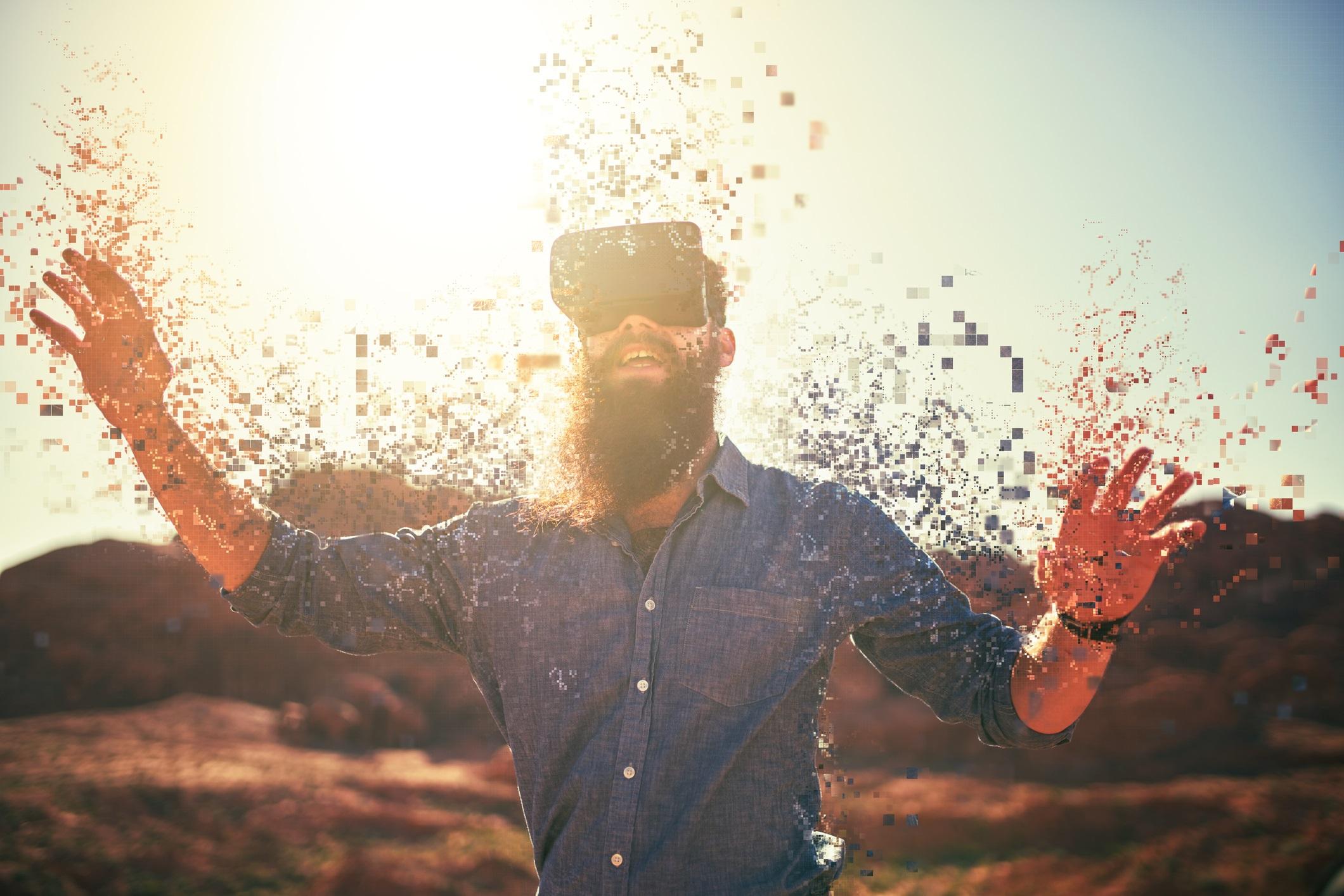 Guy wearing VR headset. He has lots of pixels around his hands.