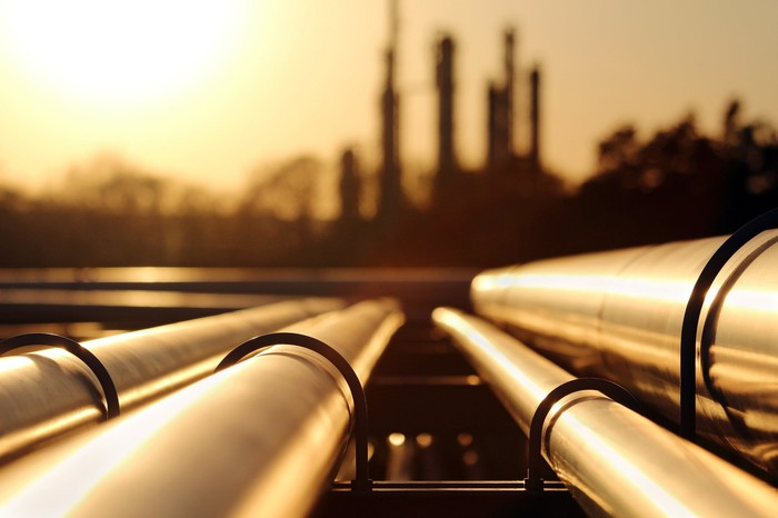 pipelines to a refinery, sunset in background