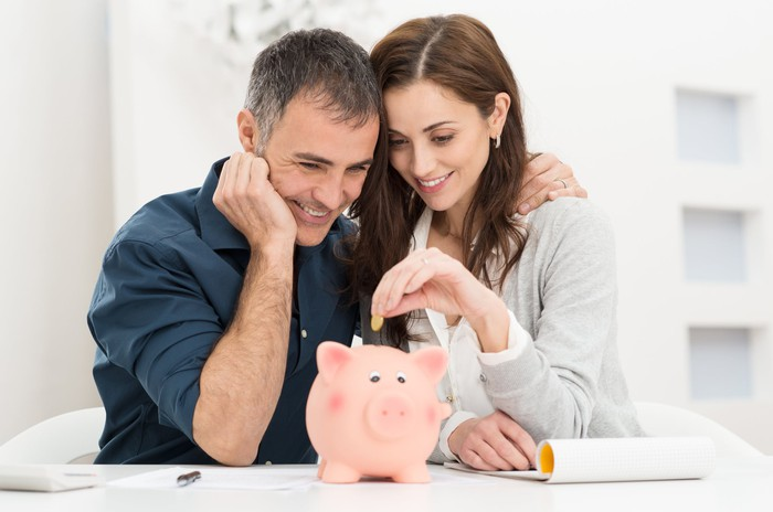 A married couple putting coins into a piggy bank.