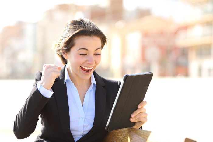 A cheering businesswoman holding a tablet.