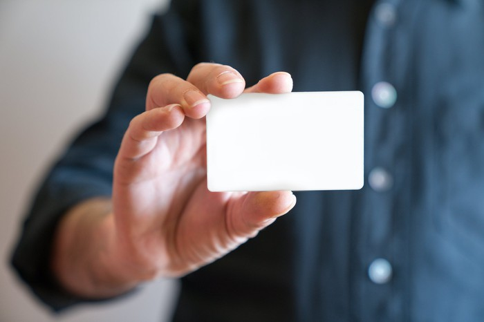 Man's hand holding a blank white card