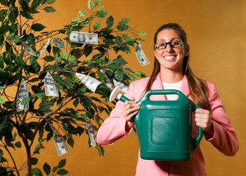 Woman Watering Money Tree Dividends Getty