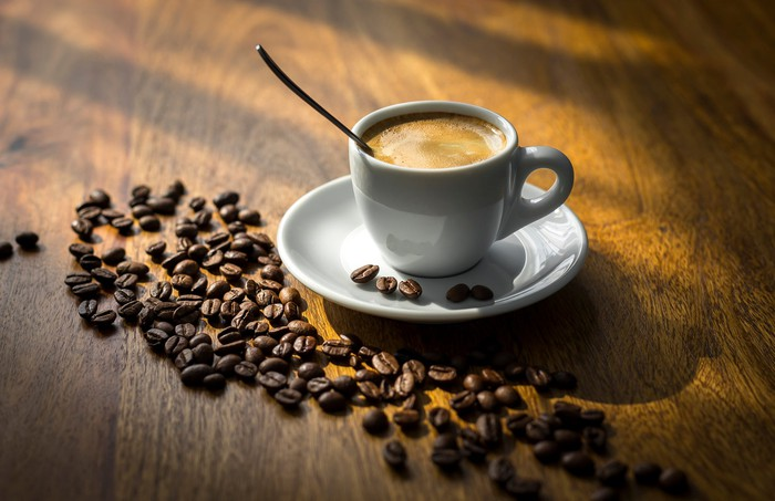 A cup of coffee sitting on a table scattered with coffee beans