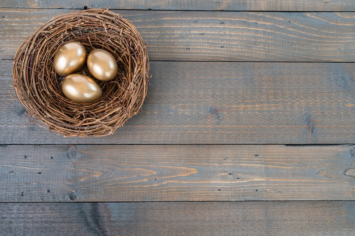 Nest with three golden eggs in it sitting on a wooden table