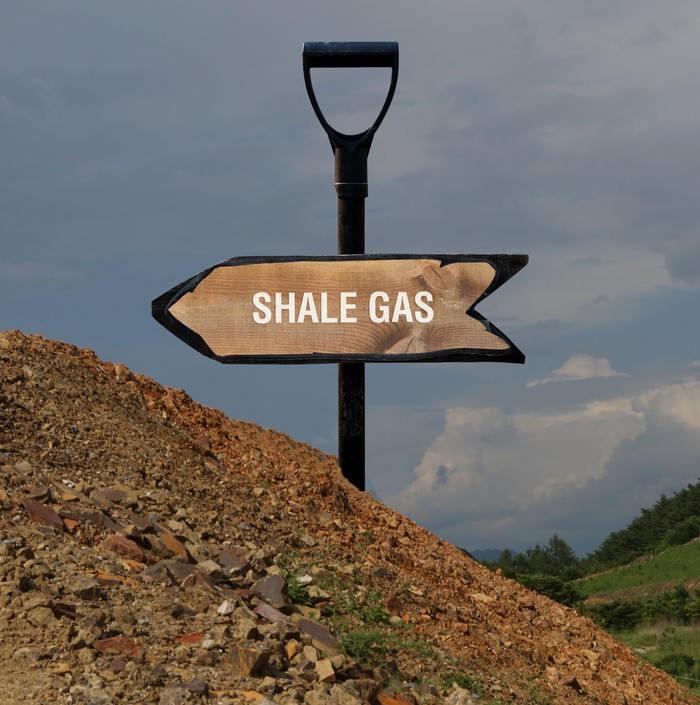 "A sign reading ""shale gas"" affixed to the handle of a shovel that's jammed into the ground."