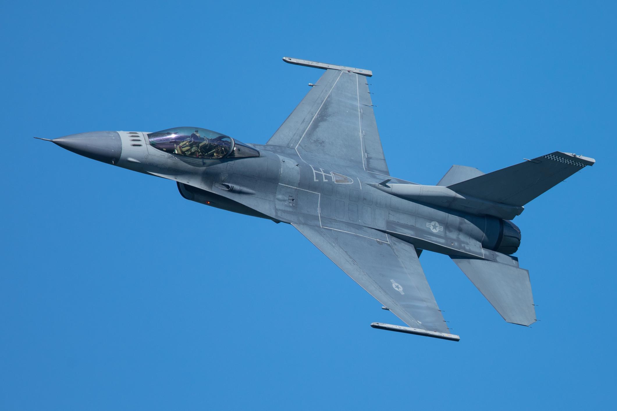 A fighter jet flies through a clear blue sky