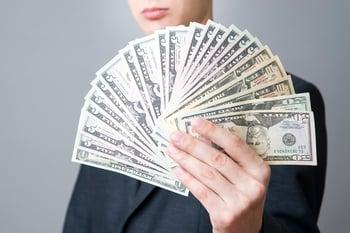Businessman Fanning Money Dividends Getty