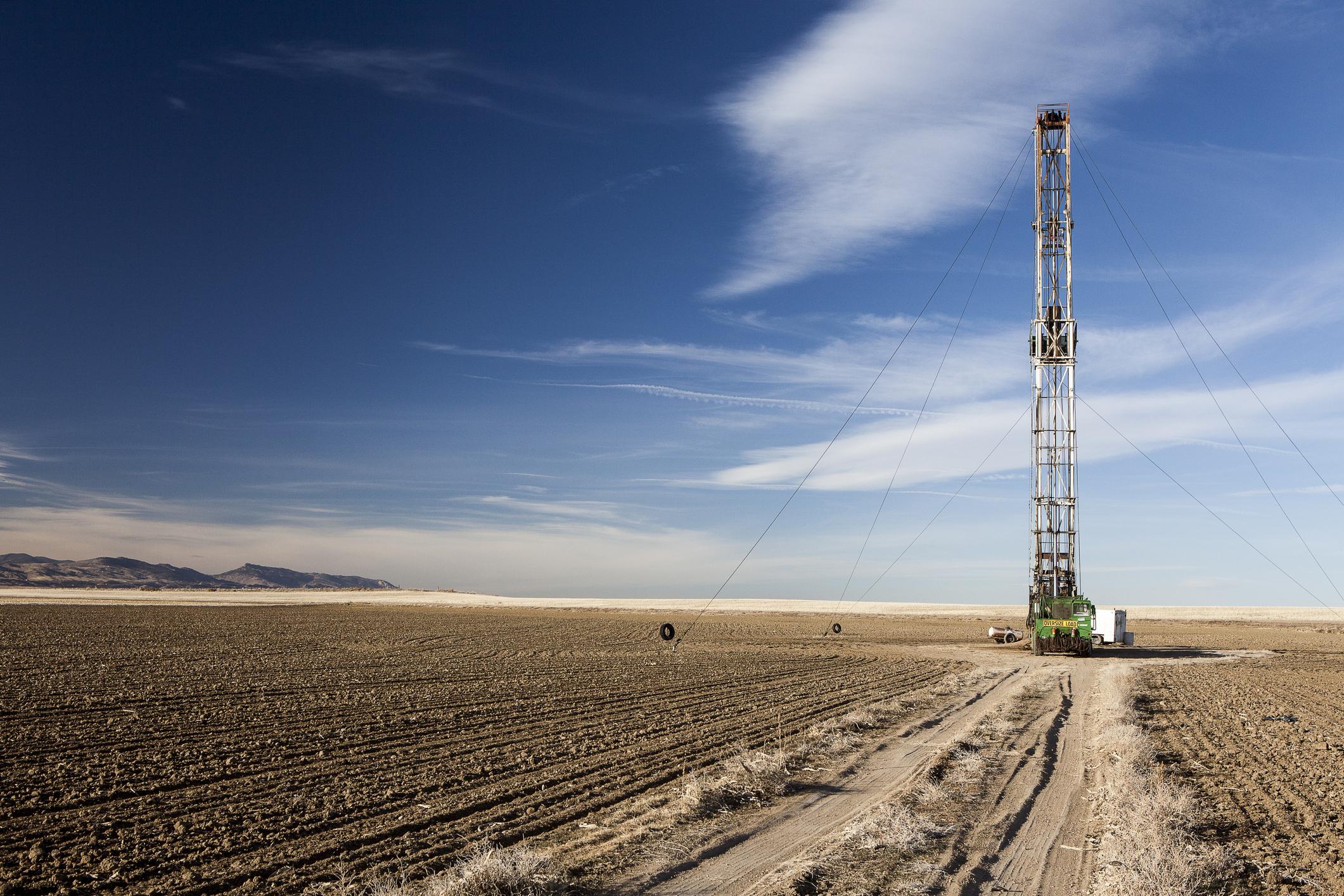 A shale drill in an open plain under a blue sky.