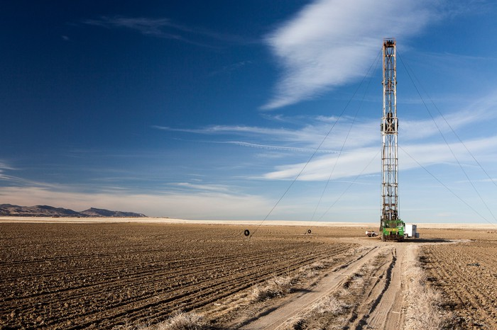 A shale drill in an open plain under a blue sky.