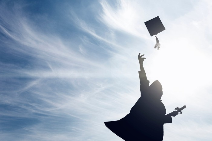 Silhouette of person throwing mortarboard into the air with a blue sky in the background