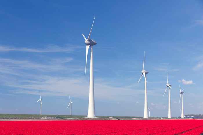 Six white wind turbines on a flat green field with a blue sky in background and a blanket of red flowers in the foreground.