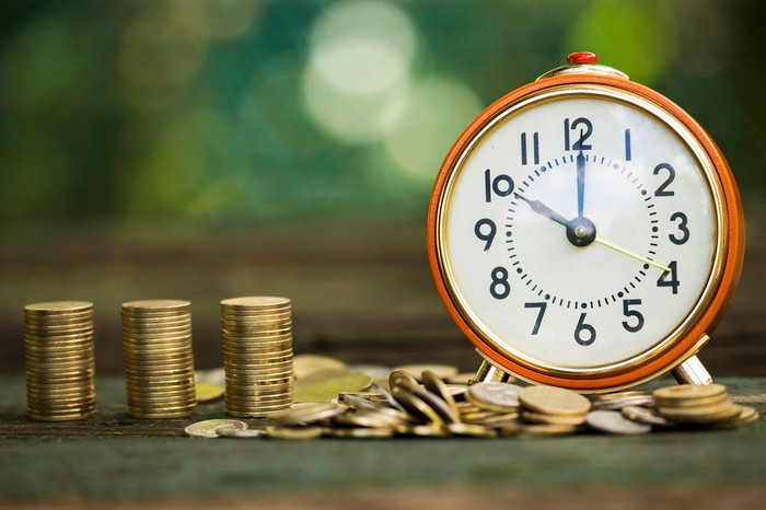 Piles of coins next to a clock
