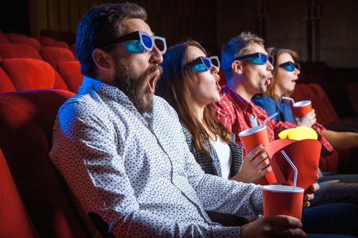 Four people in a movie theatre wearing 3D goggles with surprised looks on their faces.