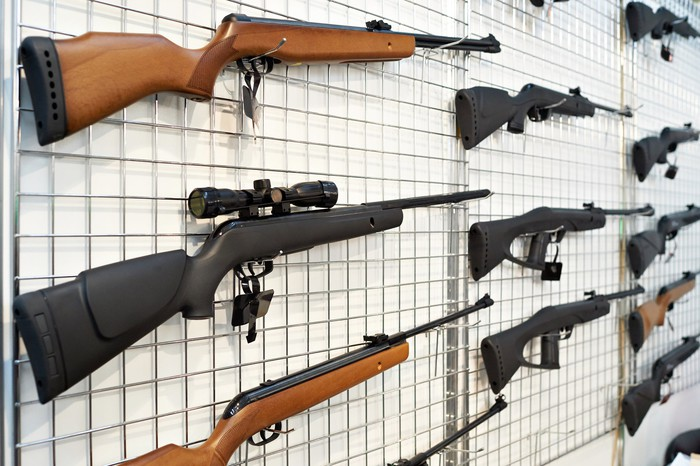 A white wall with various different rifles hanging on it.