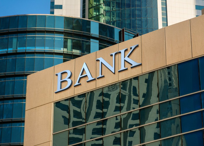 A tall building with large glass windows has the word bank written at the top of it.