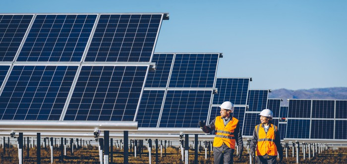 Two workers in orange vests and white hard hats walk past a field of solar panels.