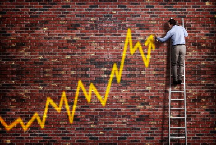 A man on a ladder spray paints an upward-trending yellow arrow on a brick wall