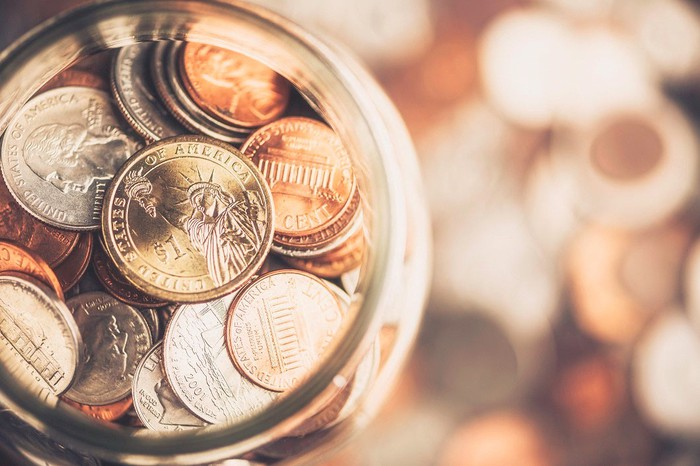 Coin jar on top of blurred coins in background