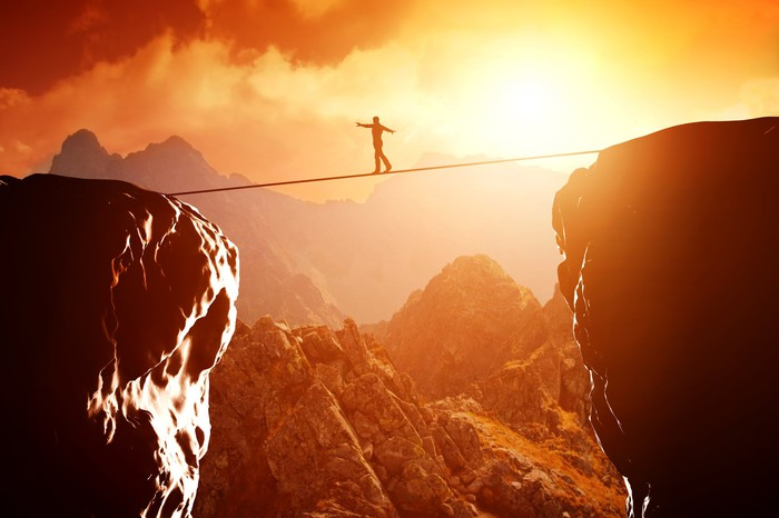 Man walking on tightrope between two cliffs with sun setting in the background