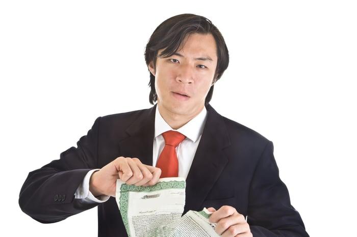 Man splitting a stock certificate in half.