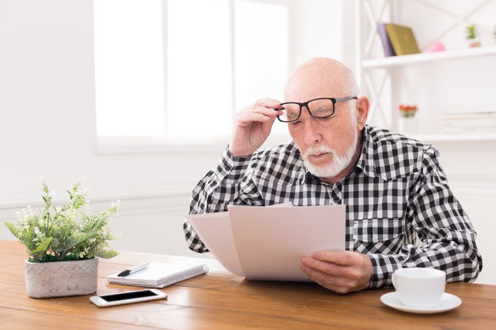 Senior man with his glasses raised slightly reading important documents while sitting at a desk with a plant, an iphone, a paid, and a coffee cup.