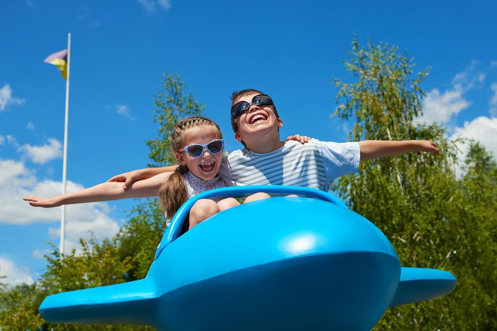 Two children on an airplane attraction at an amusement park
