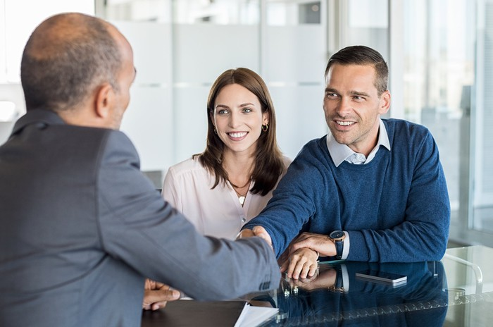A financial advisor shakes hands with a client couple.