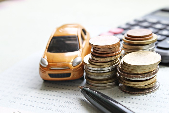 Miniature car next to three stacks of coins, a pen, and a calculator