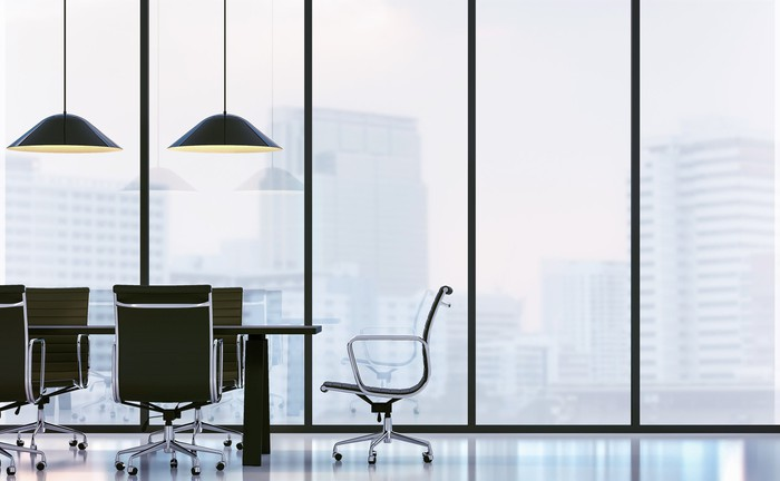A large conference room with floor-to-ceiling glass windows looking out onto a big city