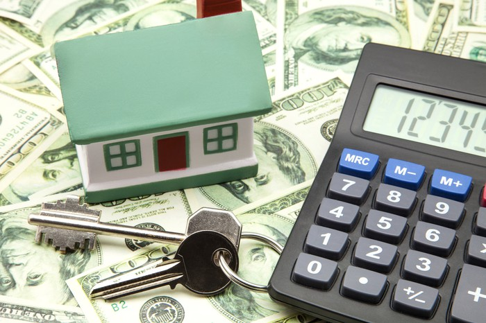 A small model home sits atop money next to house keys and a calculator.