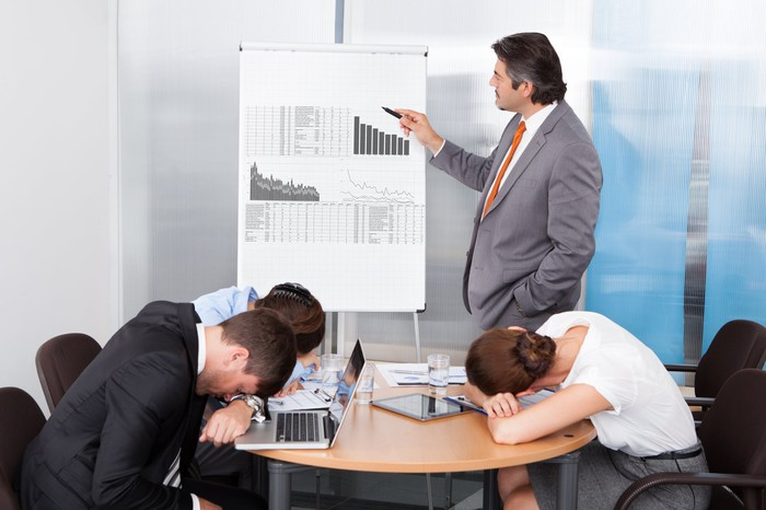 Man in suit pointing to charts while people sleep at the conference table.