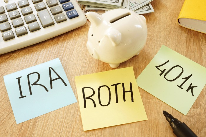 Calculator, cash, and a piggy bank next to Post-it notes with IRA, ROTH, and 401k written on them