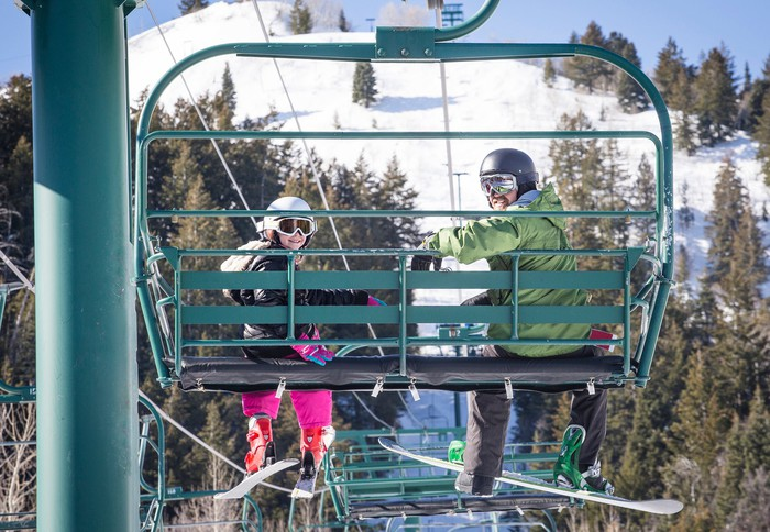 Adult and child on a ski lift with trees and hill in background