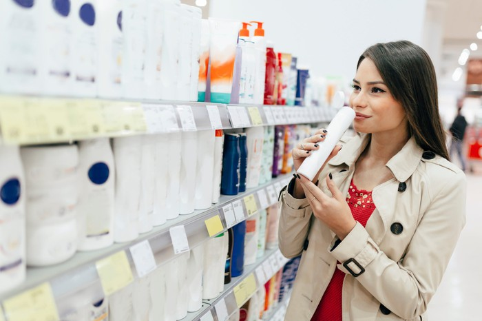 A woman buying shampoo in a supermarket