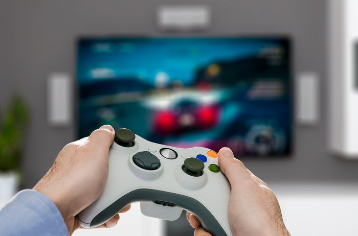 A pair of hands holding a white video game controller in front of a TV