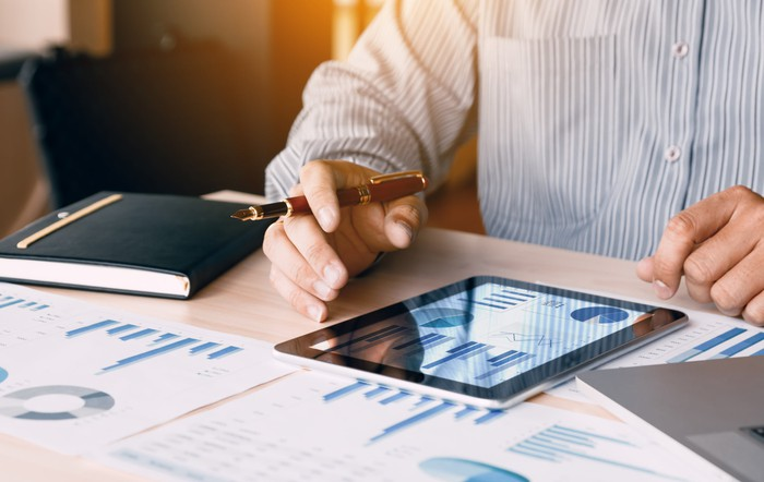 A man working at a desk with a tablet and lots of financial charts