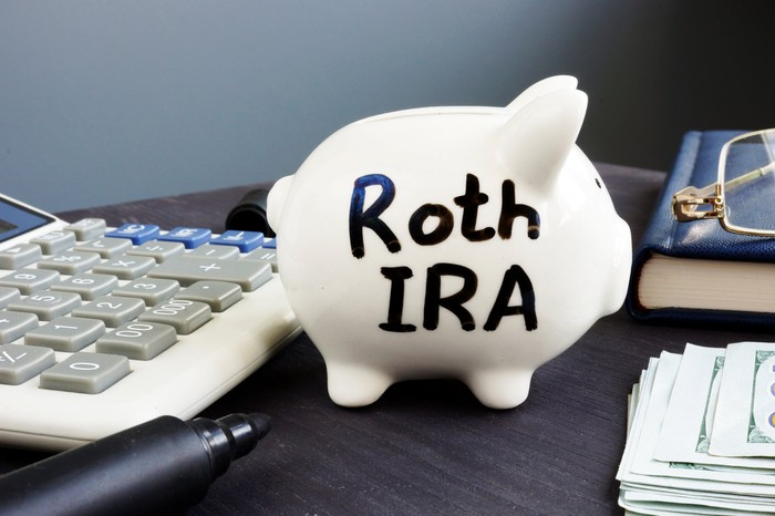 Roth IRA written with a thick black marker on a white piggy bank that's standing next to a calculator, a book, and a pair of eyeglasses.