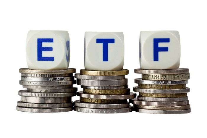 The letters ETF on three piles of coins.