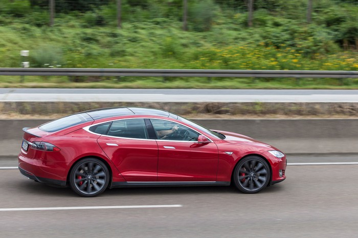 Red Tesla driving down the road
