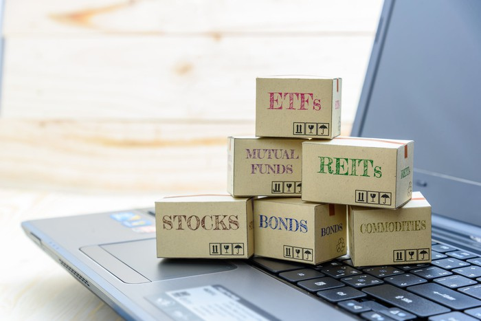 """Small boxes labeled """"STOCKS,"""" """"MUTUAL FUNDS,"""" ETFs,"""" etc., sitting on a laptop keyboard"""