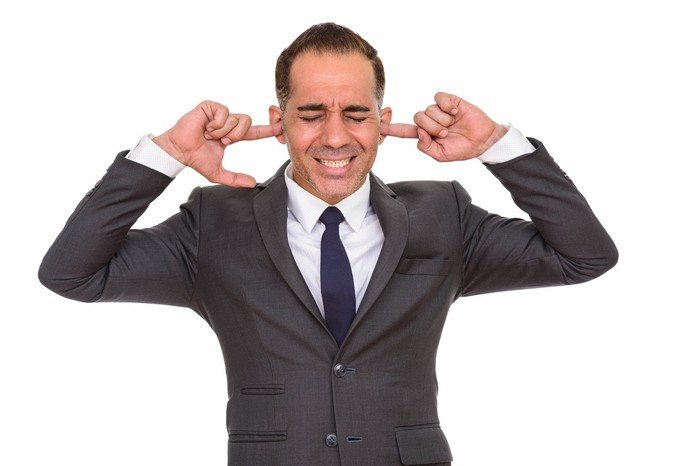 Man with eyes closed wearing suit and plugging ears